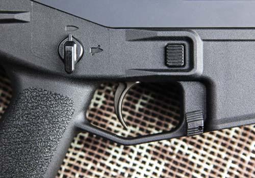 Управление винтовкой— полностью двухстороннее. Кнопка выброса магазина (а) и рычаг предохранителя (б) находятся там же, что и у AR-15. А затворная задержка переместилась в основание спусковой скобы (в)